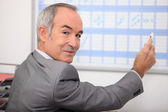 Grey haired man writing on calendar — Stock Photo
