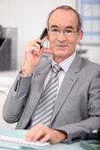 Older businessman using a cellphone — Stock Photo