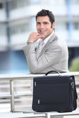 Smiling businessman and briefcase — Stock Photo