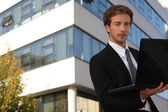 Young executive in front of building — Stock Photo