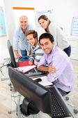Four smiling gathered round a computer in a classroom — Stock Photo