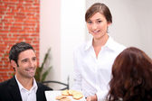 Waitress delivering meal in restaurant — Stock Photo