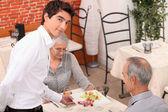 Joven camarero que sirve par senior en restaurante — Foto de Stock