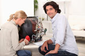 Couple repairing broken television — Stock Photo