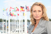Businesswoman with flags — Stock Photo