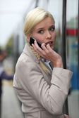 Blonde woman at phone having an anxious face expression — Stock Photo