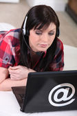 Woman using a headset over the internet — Stock Photo