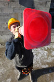 Builder shouting through traffic cone — Stock Photo