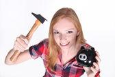 Amusant coup de jeune fille essayant de forcer ouvre sa tirelire avec un hamme — Photo