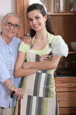 Young woman in an apron with an elderly lady — Stock Photo