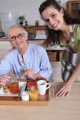 An old woman having breakfast with a younger woman — Stock Photo