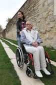 Young woman with elderly woman in wheelchair — Stock Photo