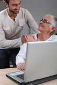 Son helping mother on laptop — Stock Photo