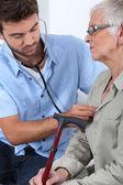 年轻的医生与老年患者 — 图库照片
