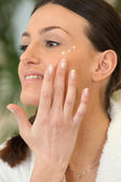 Brunette applying moisturiser — Stockfoto