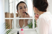 Woman applying lipstick face to the mirror — Stock Photo
