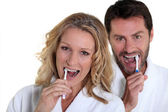 Woman and man brushing teeth — Stok fotoğraf