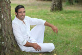 Man in white sitting by a tree — Stock Photo