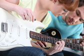 Girl learning to play guitar — Stock Photo