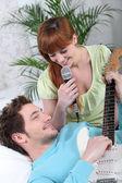 Genç bir çift bir gitar ve bir mikrofon ile — Stok fotoğraf