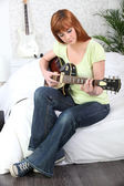 Young female guitarist at home — Stock Photo