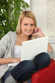Blond girl with laptop computer sitting on a sofa — Stock Photo