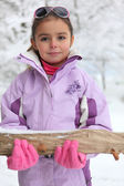 Little girl carrying a log through the snow — Stock Photo