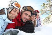 雪の中で横になっているスキー カップル — ストック写真