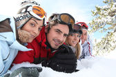 Ski couples lying in the snow — Stok fotoğraf