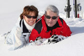 Older couple lying in the snow — Stock Photo