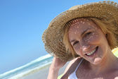 Woman at the beach wearing straw hat — Stock Photo