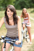 Two girls riding bikes through the forest — Stock Photo