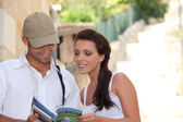Couple reading their guide during an holiday trip. — Foto Stock