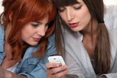 Friends looking at pictures on a mobile phone — Stock Photo