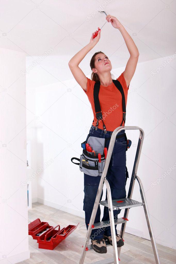 portrait d 39 une femme faisant des travaux d 39 lectricit. Black Bedroom Furniture Sets. Home Design Ideas