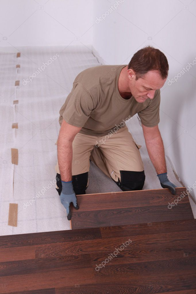Handy-man laying wooden flooring — Stock Photo #7904550