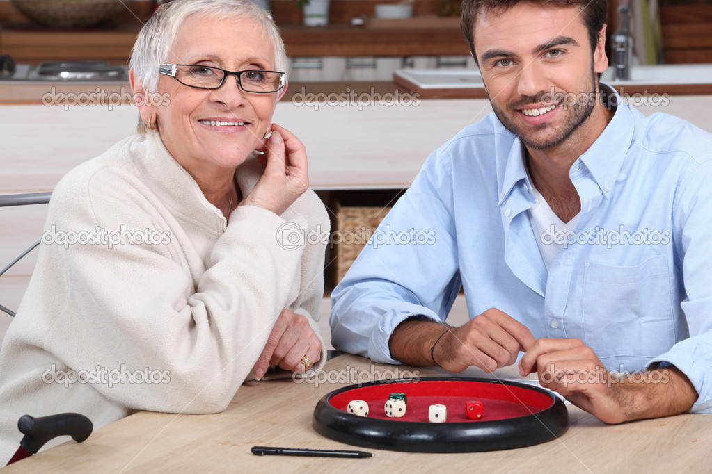 depositphotos 7906807 Young man playing dice with older woman