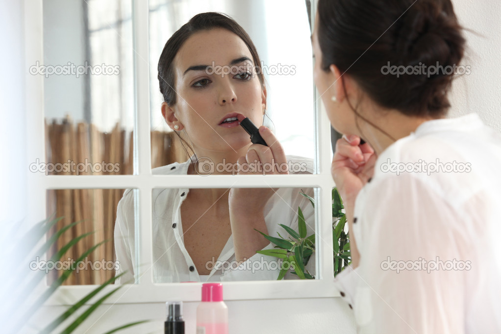 Woman applying lipstick face to the mirror — Stock Photo #7907128