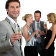 Man holding champagne glass with friends in background — Stock Photo