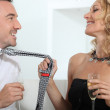 Woman drinking champagne whilst grabbing mans tie — Stock Photo #7910154