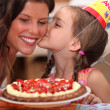 Stock Photo: Daughter kissing mommy at birthday party