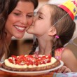 Daughter kissing mommy at birthday party — Stock Photo #7910347