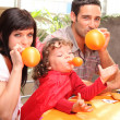 Family inflating balloons for Halloween - Stock Photo