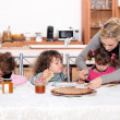 Young children eating crepes - Stock Photo