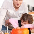 Dad and his daughter carving pumpkins in the kitchen — Stock Photo #7910697