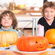 Little boy and girl dressed in pajamas posing behind pumpkins — Stock Photo