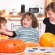 Three sisters carving pumpkins. — Stock Photo