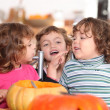 Three kids in a kitchen at Halloween time — Stock Photo