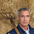 Farmer holding pitchfork — Stock Photo #7910761