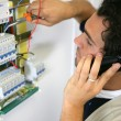 Stock Photo: Electrician working on the fuse board